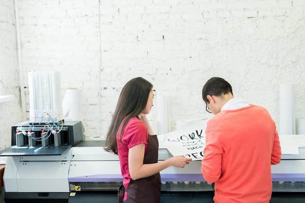 Afdrukspecialisten die banner in bureau onderzoeken
