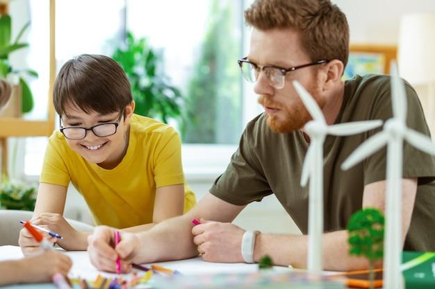 Affiche over milieu. glimlachende donkerharige jongen die geïnteresseerd is in cognitief project terwijl hij naast zijn leraar tekent