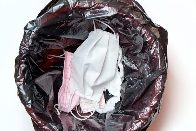 Afgedankte medische handschoenen en beschermende maskers in de prullenbak na quarantaine