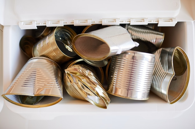 Afgedankte metalen blikjes opgeslagen in een plastic bak en klaar voor recycling, afval sorteren concept
