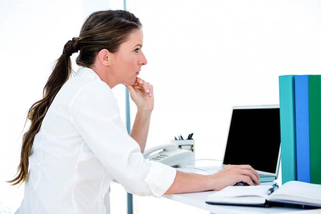 Afgeleid zakelijke vrouw, aan haar bureau op haar laptop