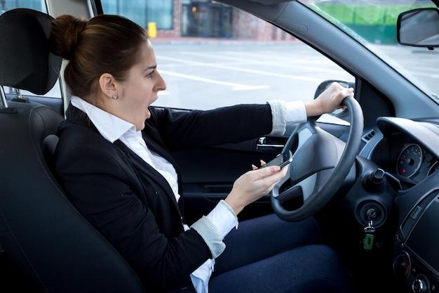 Afgeleide vrouw die smartphone gebruikt tijdens het autorijden