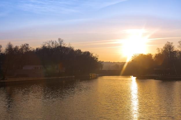 Afgelopen herfstzonsondergang over het meer in het stadspark het pad van de zon op de waterlens flare