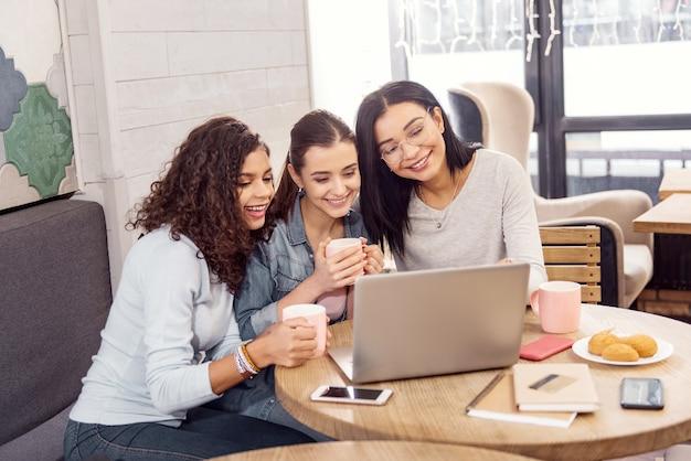 Afgemaakt werk. enthousiaste vrolijke drie studenten die lachend naar het scherm staren en laptop gebruiken