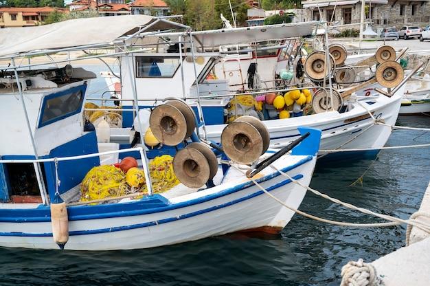 Afgemeerde boten met veel visaccessoires in de zeehaven, egeïsche zee in ormos panagias, griekenland