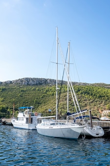 Afgemeerde boten op de pier in een dorp, veel groen, groen griekenland