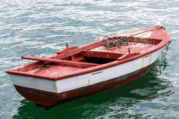 Afgemeerde rood-witte boot gemaakt van metaal en hout