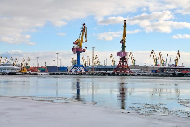 Afgemeerde vrachtschepen en havenkranen in de haven. zeehaven, vrachtcontainerwerf, containerschipterminal, scheepswerf. zaken en commercie, logistiek Premium Foto