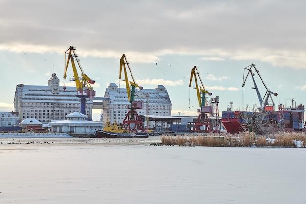 Afgemeerde vrachtschepen en havenkranen in de haven. zeehaven, vrachtcontainerwerf, containerschipterminal, scheepswerf. zaken en handel, logistiek. winter industriële scène.