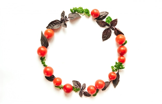 Afgerond frame van cherrytomaten, paarse basilicumbladeren en peterselie