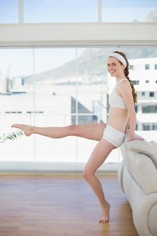 Afgerond vrouw het uitrekken zich been in geschiktheidscentrum