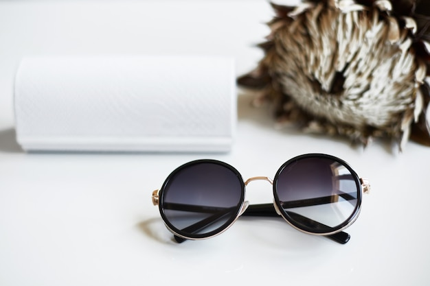 Afgeronde stijlvolle en modieuze zonnebril met hoesje en bloem op witte achtergrond