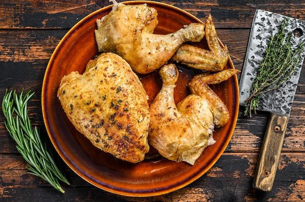 Afgeslacht gebakken kip op houten tafel. donkere achtergrond. bovenaanzicht.