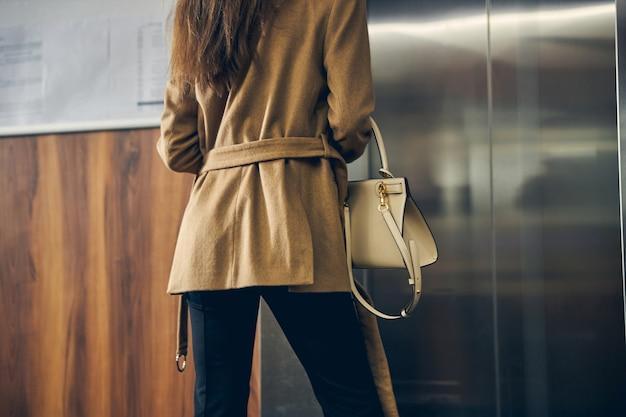 Afgesneden foto van vrouw in trendy jas met tas die op kantoor in de buurt van lift blijft