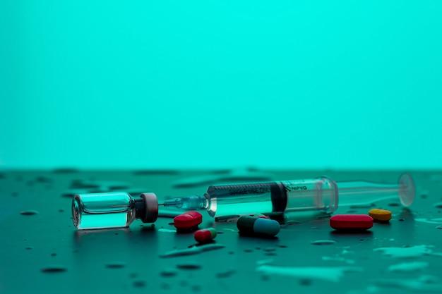 Afgestemde spuit met geneeskunde liggend tussen druppels water. het concept van medische instrumenten.