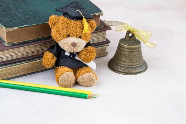 Afgestudeerd in afgestudeerde pet, oude boeken, twee potloden en een bel