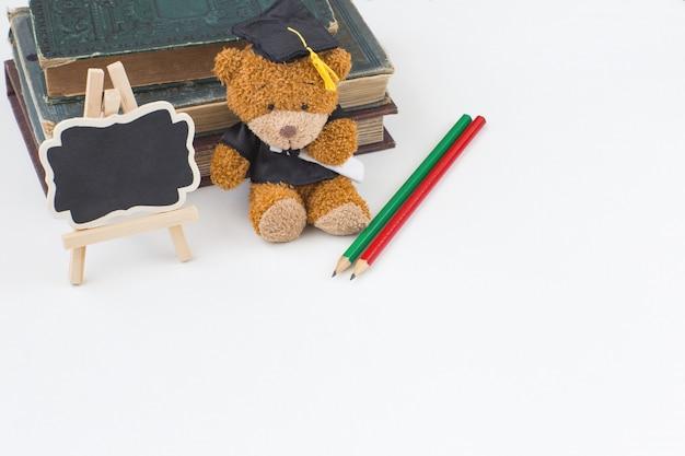 Afgestudeerd in een afgestudeerde pet, oude boeken, een inscriptiebord en twee potloden