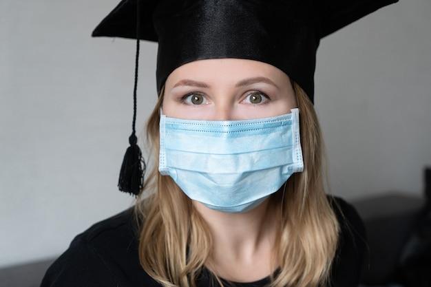 Afgestudeerd meisje met medisch masker met afstudeerjurk hoed op grijze achtergrond