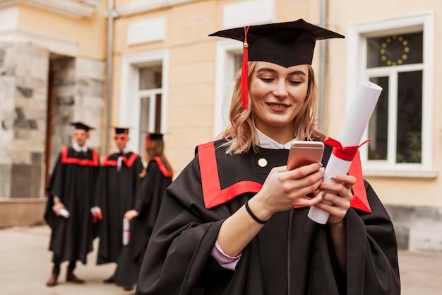 Afgestudeerd meisje met mobiel