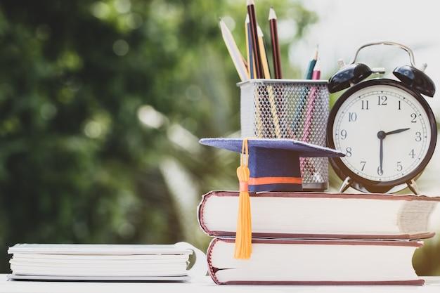 Afgestudeerd of onderwijs kennis studeren in het buitenland concept afstuderen glb op leerboek met potlood doos