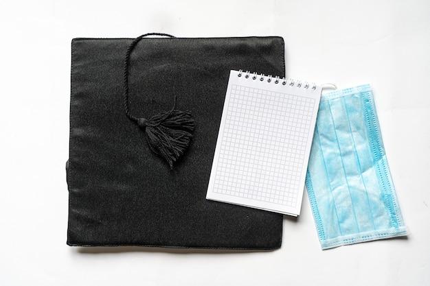 Afgestudeerde hoed, een notitieboekje en een gezichtsmasker op een witte achtergrond, plat gelegd