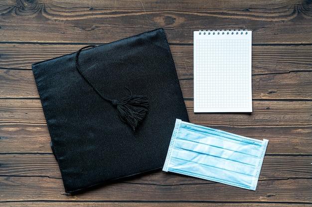 Afgestudeerde hoed, een notitieboekje en een gezichtsmasker op houten ondergrond, plat gelegd