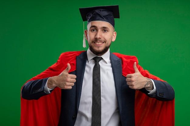 Afgestudeerde man in rode cape met blij gezicht duimen opstaande over groene muur