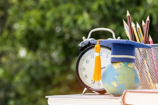 Afgestudeerde of educatieve kennisstudie in het buitenland: gaduation cap op leerboek met potlood