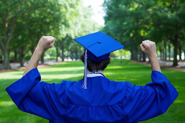Afgestudeerde student in een blauwe mantel die zijn vuisten omhoog houdt