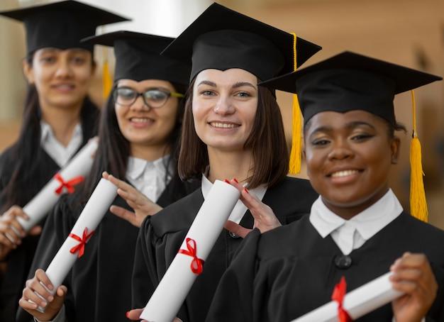 Afgestudeerde studenten die een middelgroot schot van pet en toga dragen