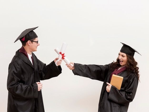 Afgestudeerde studenten vechten met diploma's