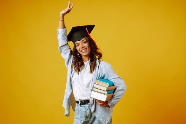 Afgestudeerde vrouw in een afstudeerhoed op haar hoofd, met boeken over geel.