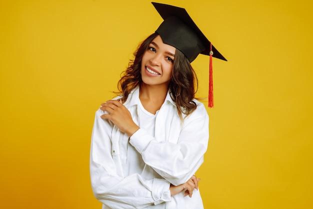 Afgestudeerde vrouw in een afstuderen hoed op haar hoofd poseren op geel