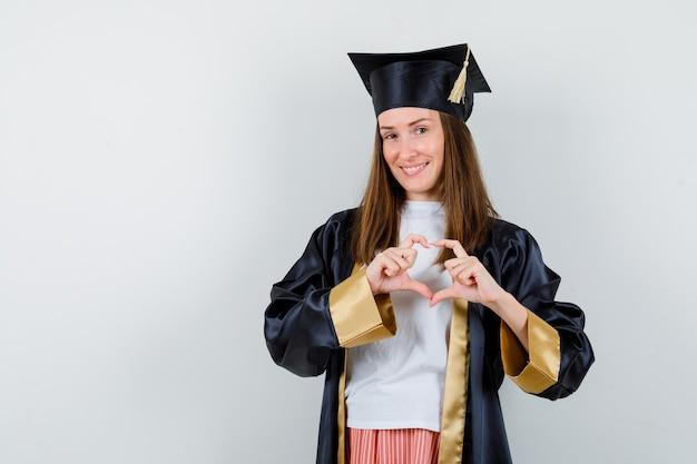 Afgestudeerde vrouw in vrijetijdskleding, uniform hartgebaar tonen en op zoek blij, vooraanzicht.