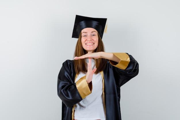Afgestudeerde vrouw in vrijetijdskleding, uniform met tijdsonderbreking gebaar en op zoek gelukkig, vooraanzicht.