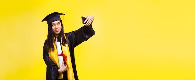 Afgestudeerde vrouw maakt selfiefoto over gele ruimte