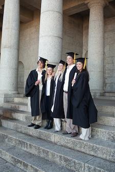 Afgestudeerden die zich voordeed terwijl glimlachen