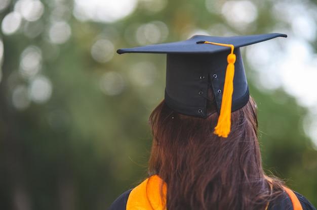 Afgestudeerden dragen zwarte academische toga op de dag van afstuderen aan de universiteit