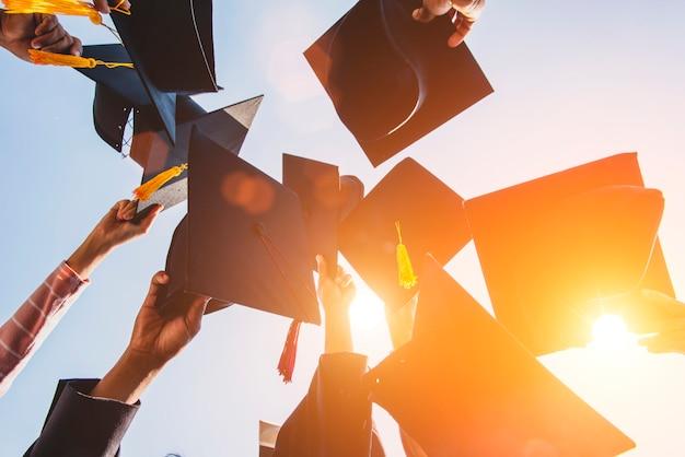 Afgestudeerden gooien de hoed op de diploma-uitreiking aan de universiteit.