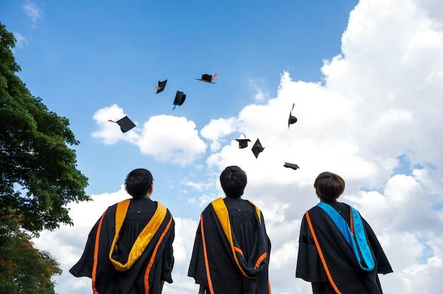 Afgestudeerden gooien hoedjes op afstudeerdag aan de universiteit.