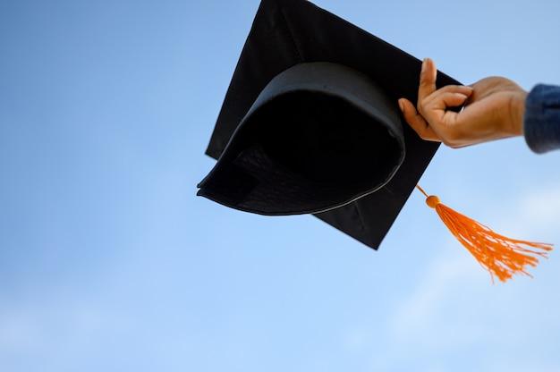Afgestudeerden houden een zwarte hoed met een gele kwast vast aan de hemel.