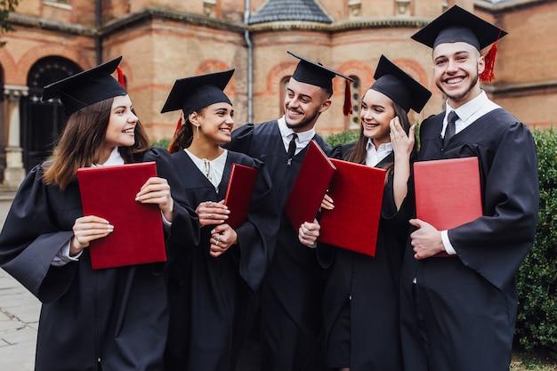 Afgestudeerden omhelzen, genieten en kijken naar de camera tijdens de diploma-uitreiking