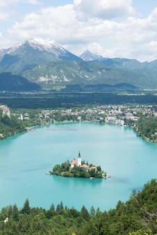 Afgetapt meer, eiland en bergen op achtergrond, slovenië, europa