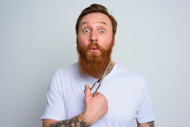 Afgevraagd man met schaar is klaar om de baard te knippen