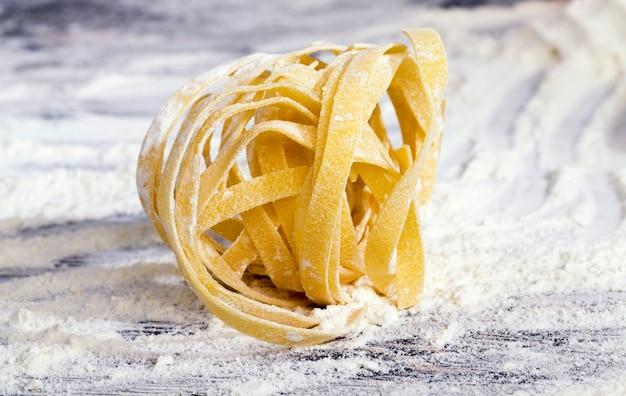 Afgewerkte droge pasta gedraaid tot een bal tarwemeel van harde tarwe, samen met bloempoeder liggen
