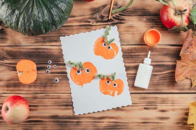 Afgewerkte halloween-kaart gemaakt met pompoenappelprints ligt naast lijm en verf op houten oppervlak, bovenaanzicht