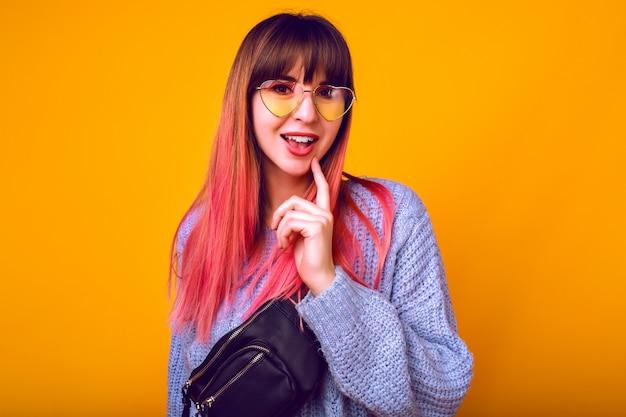 Afgezwakt portret van verlaten gelukkige vrouw met ongebruikelijke trendy ombre roze haren poseren bij gele muur, verrast emoties, gezellige trui en vintage zonnebril.