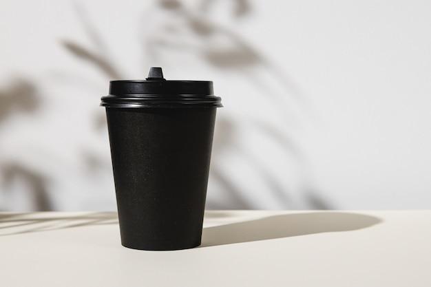 Afhaal koffiekopje met schaduwen van bladeren, kopieer ruimte