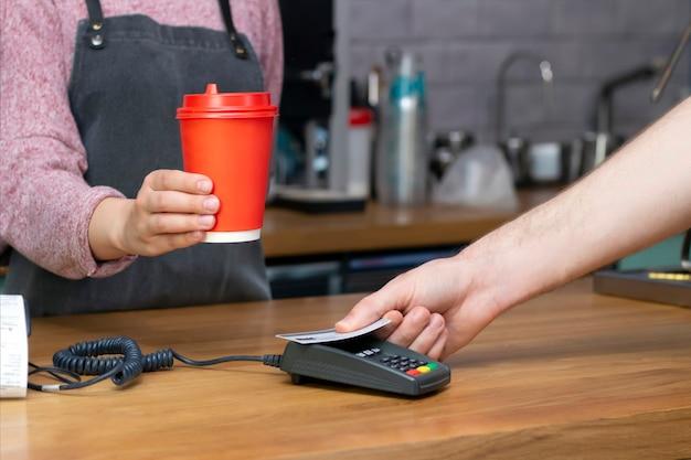 Afhaalkoffie. barista houdt een rood papieren glas vast met een drankje, de koper betaalt met een kaart