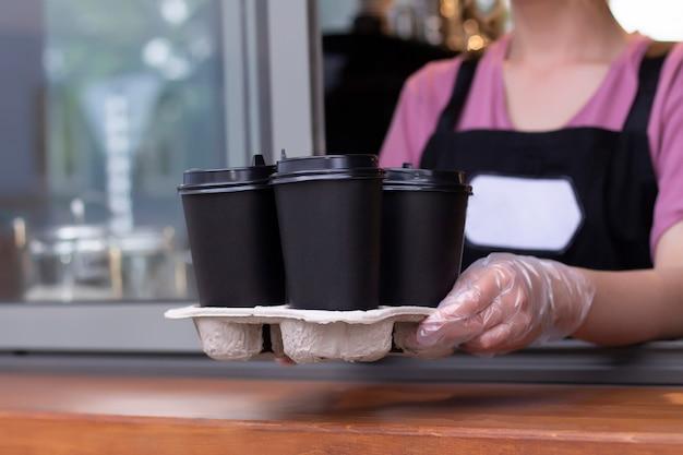 Afhaalkoffie. barista in een schort houdt warme koffie in een kartonnen beker in zijn handen